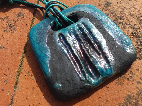 Immagine di una collana raku con particolare del ciondolo