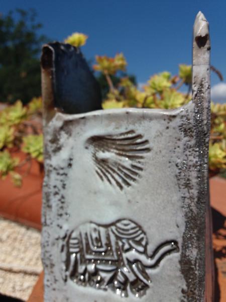 Immagine di unn vaso raku bianco con elefante particolare