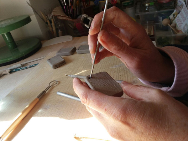 Immagine di come viene incisa l'argilla per i portachiavi in ceramica