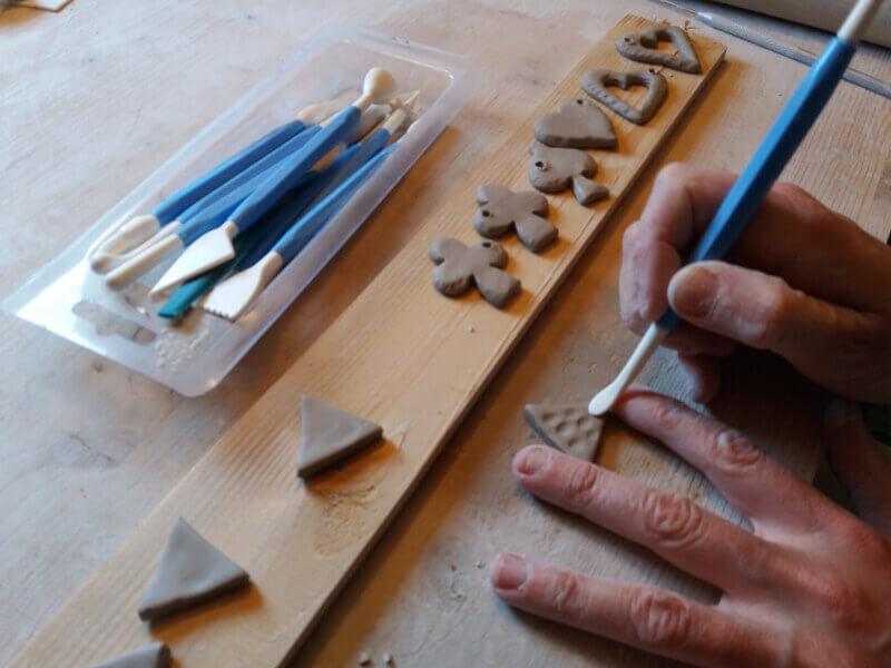 Immagine dell'uso di strumenti per dare forma agli orecchini in ceramica