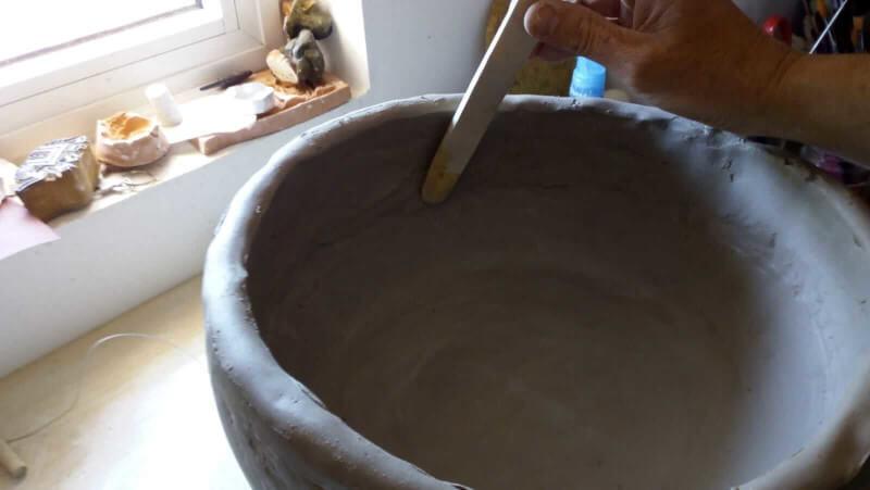 Immagine della fase di rifinitura del sottovaso in ceramica creato con i colombini