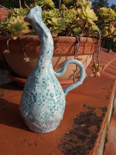 Immagine di un vasetto ceramica con collo piegato e altre creazioni primo piano