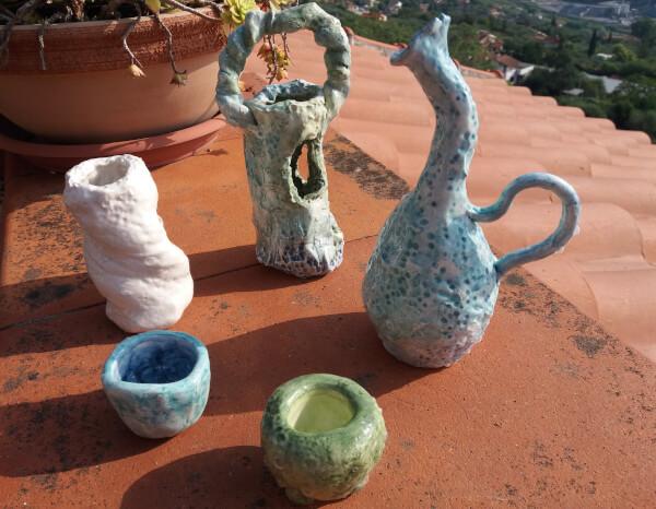 Immagine di un vasetto ceramica con collo piegato e altre creazioni vista totale